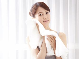 保湿に気を使って、タオルでやさしく顔を拭く女性